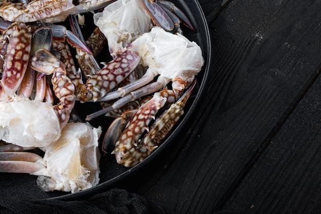 Ensemble de pièces de crabe de natation bleu frais, sur plaque, sur fond de table en bois noir, avec fond et espace pour le texte