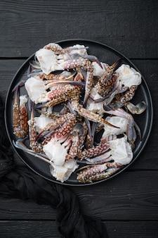 Ensemble de pièces de crabe de natation bleu frais, sur plaque, sur fond de table en bois noir, vue de dessus à plat