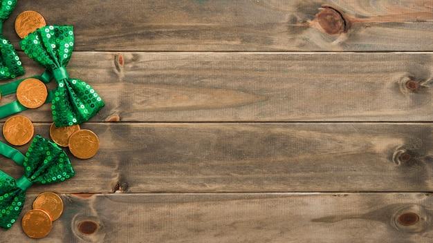 Ensemble de pièces d'or et de noeuds papillon sur planche de bois
