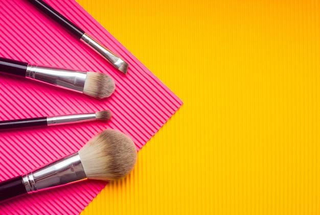 Ensemble de pinceaux de maquillage sur fond multicolore.