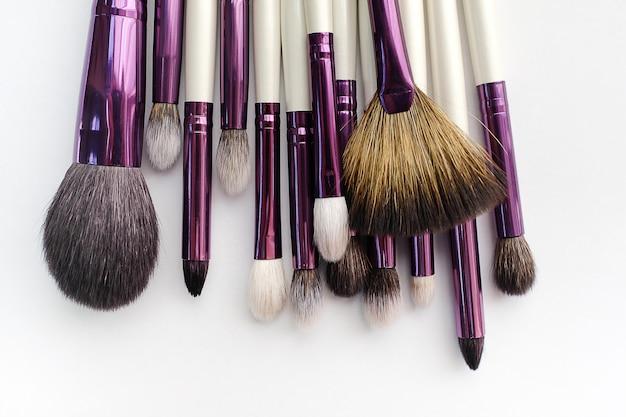 Ensemble de pinceaux de maquillage pour maquillage professionnel dans un salon de beauté, sur fond blanc. le concept des cosmétiques, des soins du corps et du visage.