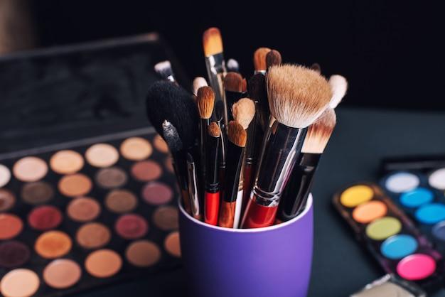 Ensemble de pinceaux de maquillage professionnels sur une palette avec des ombres à paupières colorées