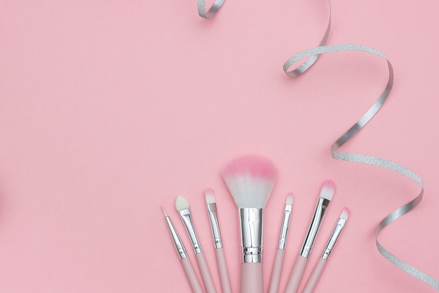 Ensemble de pinceaux de maquillage et serpentine de ruban argenté sur fond rose pastel