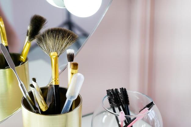 Un ensemble de pinceaux de maquilleuse pour le maquillage professionnel sur une table blanche devant le miroir