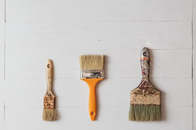 Ensemble de pinceaux avec de la peinture sur la teinture en bois blanc
