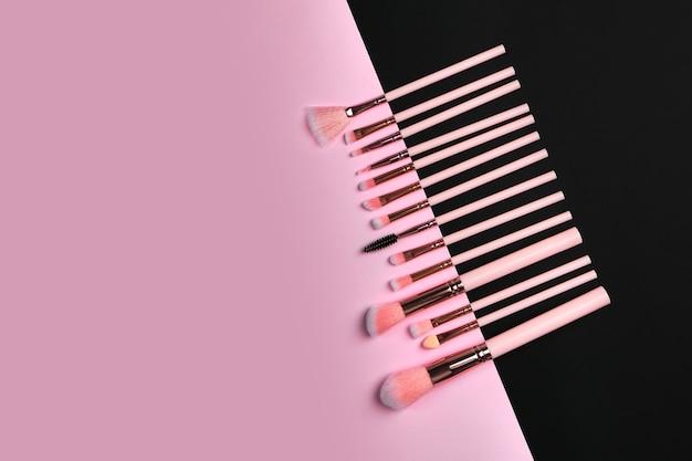 Ensemble de pinceaux professionnels sur une surface composée de couleur noire et rose