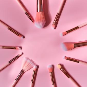 Ensemble de pinceaux professionnels sur une surface rose repliée