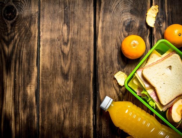 L'ensemble de pique-nique. sandwiches au fromage et bacon, fruits et jus d'orange.