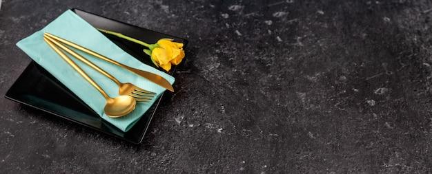Ensemble de plaque carrée noire élégante et couverts en or sur fond noir