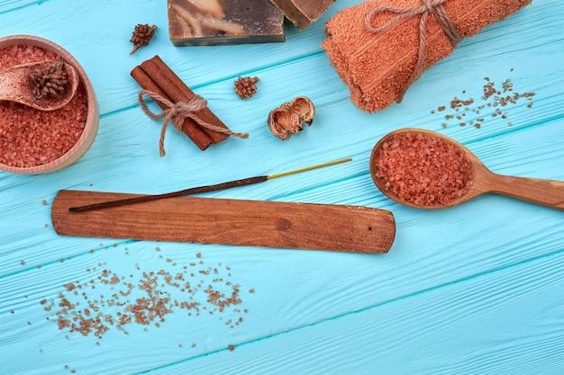 Ensemble plat d'accessoires de salle de bain sur un bureau en bois bleu. sel avec bâton et cannelle.