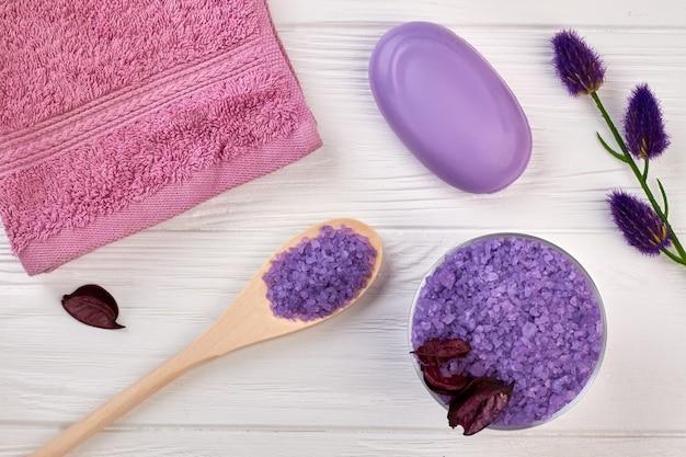 Ensemble plat d'accessoires violets pour le traitement au spa. savon serviette sel et cuillère sur table en bois blanc.