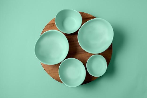 Ensemble plat de bols vides peints dans la couleur à la mode de 2020 néo menthe sur le fond de la même teinte.
