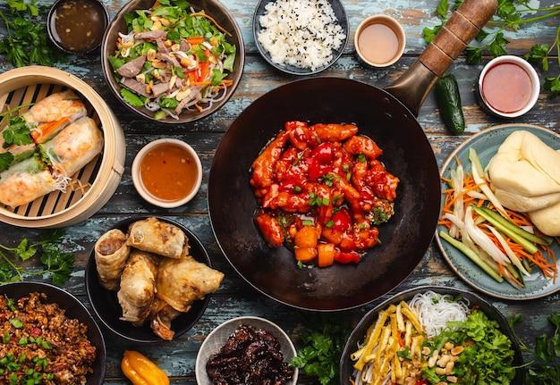 Ensemble de plats chinois assortis sur table : poulet aigre-doux dans un wok, dim sum dans un cuiseur vapeur en bambou, rouleaux de printemps, nouilles, salade, riz, petits pains cuits à la vapeur, trempettes. dîner ou buffet de style asiatique, vue de dessus