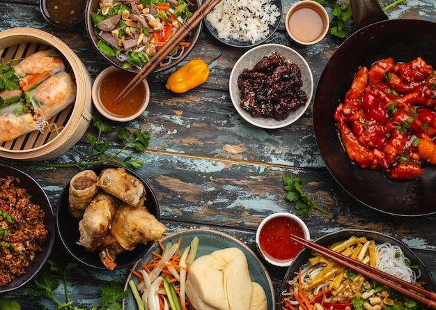Ensemble de plats chinois assortis sur table : poulet aigre-doux dans un wok, dim sum, rouleaux de printemps, nouilles, salade, riz, petits pains cuits à la vapeur. dîner ou buffet de style asiatique avec vue de dessus et espace pour le texte