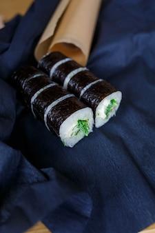 Ensemble de plats japonais traditionnels. rouleaux de sushi, nigiri, saumon cru, riz, fromage à la crème, avocat, gingembre mariné.