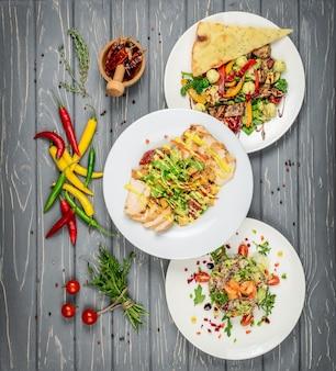 Ensemble de plats avec des salades sur la table
