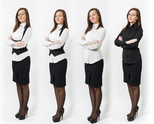 Ensemble de pleine longueur jolie jeune femme d'affaires souriante aux cheveux bruns en chemise classique noire et blanche, jupe, lunettes tenant les mains croisées isolées sur mur blanc