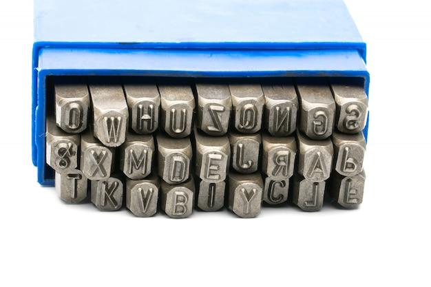 Ensemble de poinçon alphabet timbre en métal dans une boîte en plastique bleu isolé sur fond blanc
