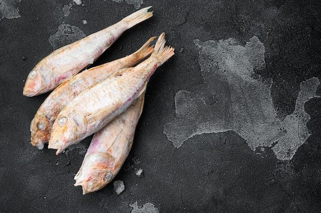 Ensemble de poisson surmullet congelé, sur fond de table en pierre noire noire, vue de dessus à plat, avec espace de copie pour le texte