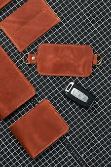 Un ensemble de portefeuilles, de porte-cartes de visite et de porte-clés en cuir fait main, en cuir rouge sur une table pour couper le cuir, entouré d'outils, démonstration de produits en cuir faits à la main.