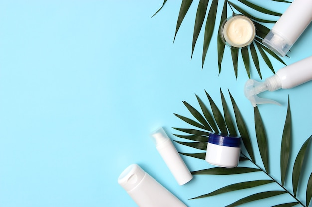 Ensemble de pots cosmétiques de couleur blanche et de branches de palmier sur fond coloré