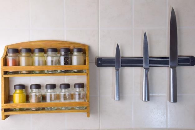 Un ensemble de pots avec différentes épices et un ensemble de trois couteaux en acier sont accrochés au mur en céramique