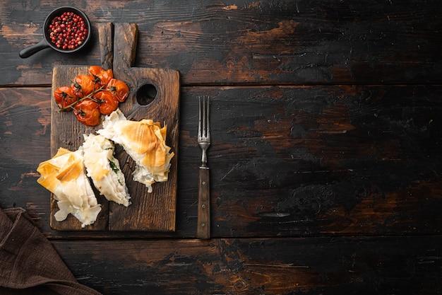 Ensemble de poulet kiev filo, avec des tomates cerises au four, sur une planche de service, sur une vieille table en bois foncé