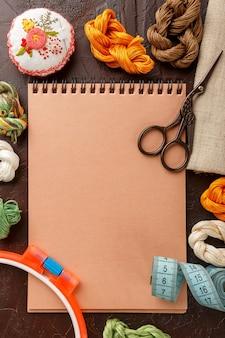 Ensemble pour broderie, cerceau à broder, toile de lin, fil, ciseaux, lit à aiguilles brodé et bloc-notes. vue de dessus