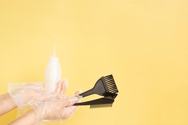 Ensemble pour la teinture des cheveux à la maison ou au salon dans les mains d'une femme avec des gants - brosses et bouteille sur fond jaune