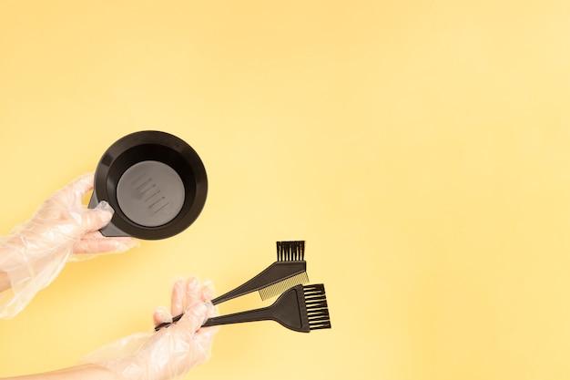Ensemble pour la teinture des cheveux à la maison ou au salon entre les mains d'une femme avec des gants. brosses et bol pour teinture capillaire sur fond jaune