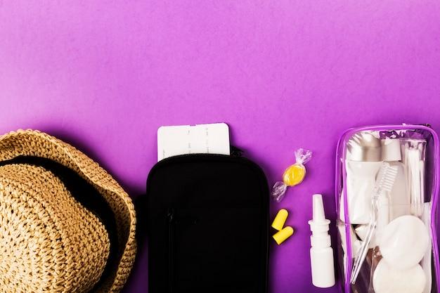 Ensemble pour le vol de petites bouteilles avec cosmétiques, chapeau, bouchons d'oreilles, spray nasal, billet d'avion et documents sur fond violet