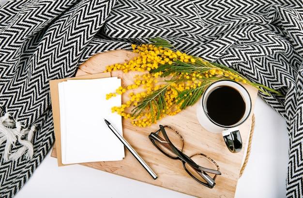 Ensemble de printemps avec des fleurs jaune plaid mimosa tasse avec des cartes postales de café stylo lunettes