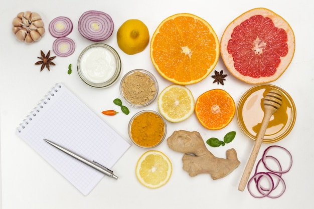 Ensemble de produits d'agrumes, gingembre, miel, ail, yaourt aux oignons. cahier et stylo sur table. remède naturel pour la prévention de la grippe. mise à plat