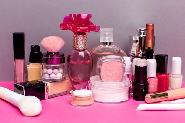 Ensemble de produits cosmétiques colorés sur une table rose