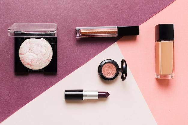 Ensemble de produits cosmétiques décoratifs sur une surface colorée