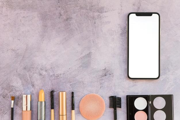 Ensemble de produits cosmétiques sur fond de béton avec téléphone intelligent