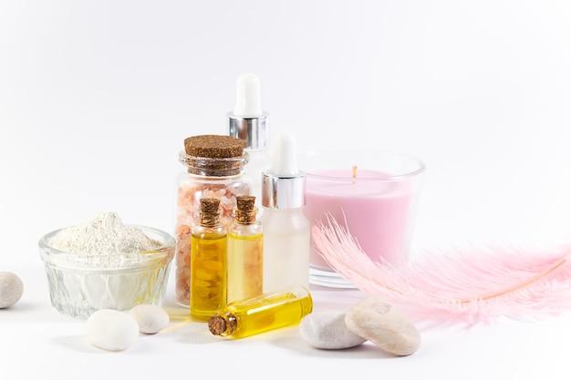 Ensemble de produits cosmétiques naturels tels que les huiles de sérums, les bougies aromatiques en argile cosmétique et les pierres de massage sur fond blanc
