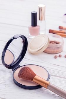 Ensemble de produits cosmétiques avec des pinceaux à maquillage. poudre, vernis à ongles et parfum