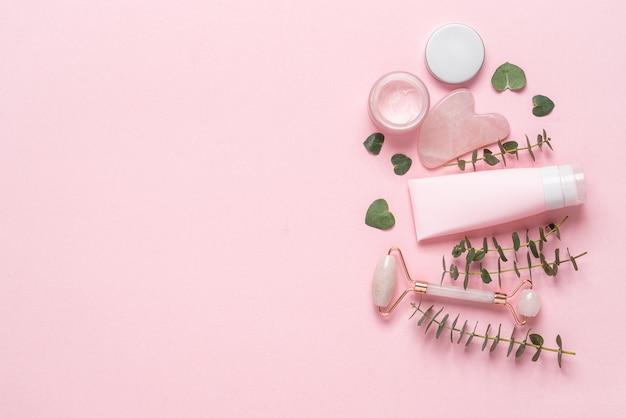 Ensemble de produits cosmétiques pour le visage et le corps. visage rouleau, masseur guasha, pot de crème, tube en plastique sur fond rose pastel