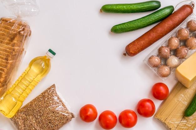 Un ensemble de produits sur fond blanc. épicerie, légumes, beurre, œufs et saucisses. paquet alimentaire