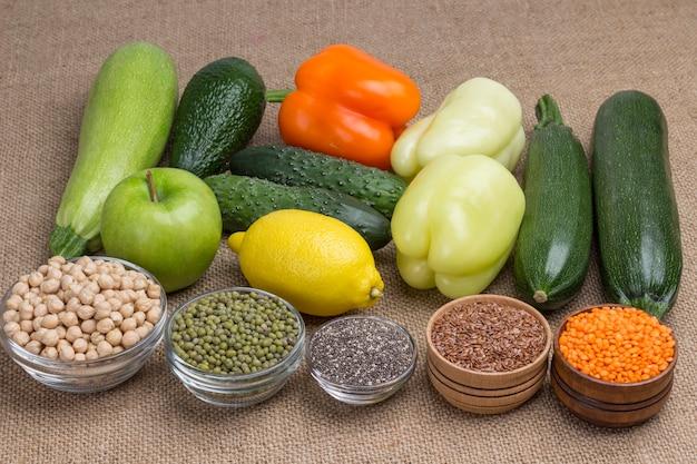 Ensemble de produits nutritionnels équilibrés avec poivre, pomme citron, quinoa, avocat, lentilles en toile de jute, graines de lin