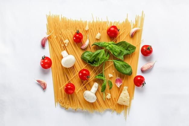 Ensemble de produits pour cuisiner des pâtes italiennes traditionnelles sur un espace blanc.