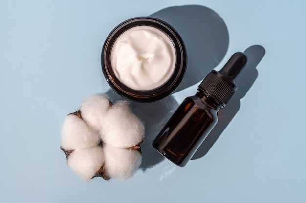Ensemble de produits de soins de la peau. huile essentielle visage et crème hydratante sur fond bleu à décor de fleur de coton. routine quotidienne dans le traitement de la peau du visage.