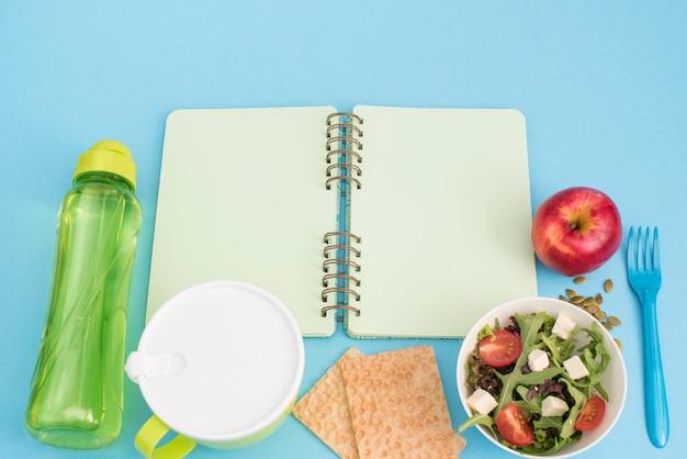 Un ensemble de produits utiles, tomates cerises, pommes fruits graines vaisselle plastique vaisselle fleurs blanches salade fraîche