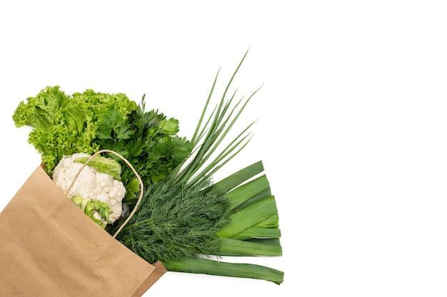 Un ensemble de produits verts dans un sac en papier. isolé sur fond blanc. faire ses courses dans un supermarché ou un marché.