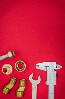 Ensemble professionnel d'outils et de pièces de rechange pour la plomberie sur un bureau rouge avec un espace pour la publicité