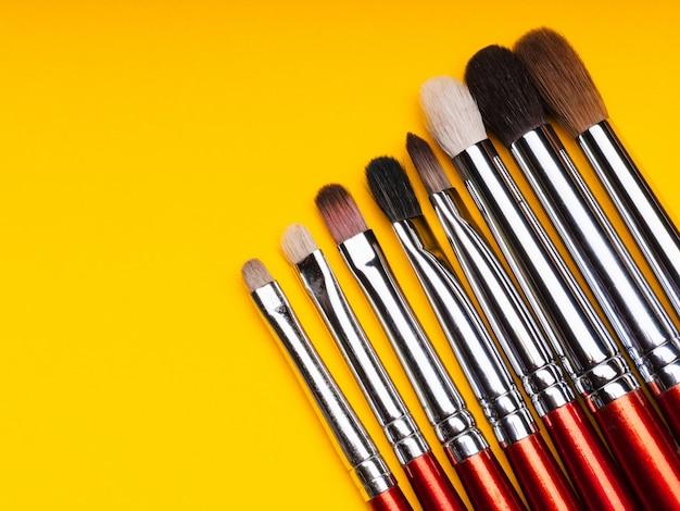 Ensemble professionnel de pinceaux de maquillage sur fond jaune