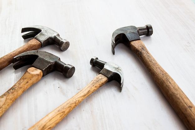 Ensemble de quatre outils de poignée de marteau vieux vintage sur le fond de couleur de peinture blanche bois