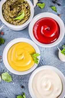 Ensemble de quatre sauces classiques: ketchup, mayonnaise, moutarde, pesto aux herbes et épices