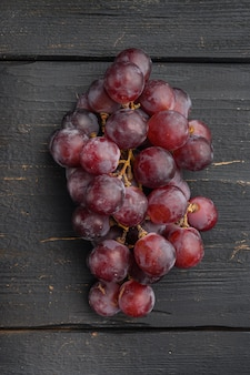 Ensemble de raisins juteux biologiques naturels, fruits rouges foncés, sur table en bois noir, vue de dessus à plat